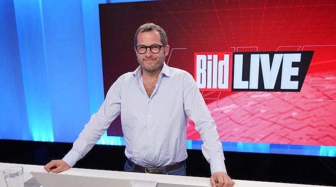 """Julian Reichelt, Chefredakteur """"Bild"""", steht im August 2021 im Studio des TV-Senders """"Bild"""". Er trägt ein weißes Hemd, lächelt in die Kamera."""