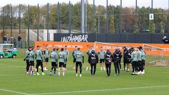 Die Spieler von Borussia Mönchengladbach stehen vor einer Trainingseinheit am 20. Oktober 2021 versammelt auf dem Platz im Borussia-Park, werden dabei von einigen Fans beobachtet.