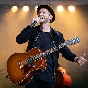 """Johannes Oerding, Popsänger und Songwriter, steht bei einem Konzert auf der Open-Air-Bühne im Stadtpark. Oerding wird auch 2022 Gastgeber der Vox-Musikshow """"Sing meinen Song""""."""