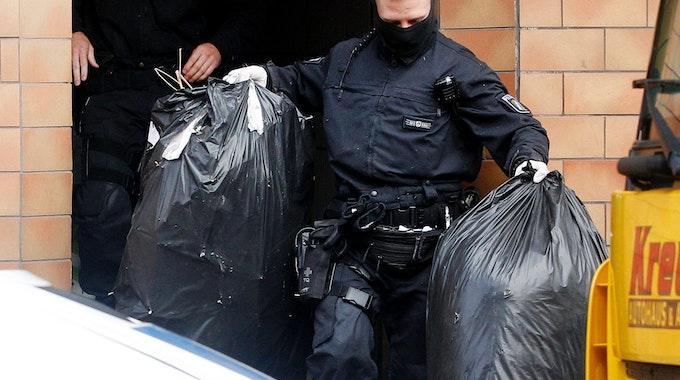Ein Polizist trägt zwei Säcke mit den Resten von Cannabis-Pflanzen aus einem Haus.
