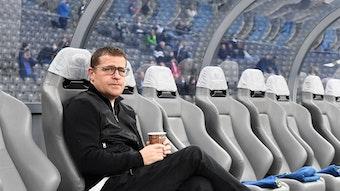 Max Eberl, Manager von Fußball-Bundesligist Borussia Mönchengladbach, sitzt vor dem Topspiel bei Hertha BSC am Samstag (23. Oktober 2021) noch ruhig auf der Ersatzbank im Olympiastadion. Eberl hält einen Getränkebecher in den Händen.