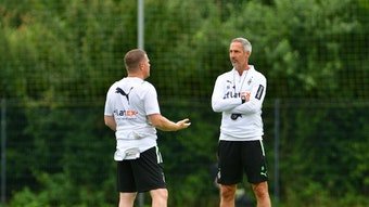 Max Eberl (l.), Manager bei Fußball-Bundesligist Borussia Mönchengladbach, unterhält sich am 21. Juli 2021 in Harsewinkel mit Cheftrainer Adi Hütter (r.). Eberl redet, Hütter hört zu.