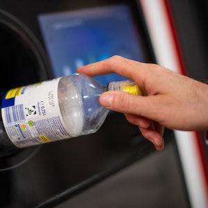 Ein Mann steckt eine Pfandflasche in einen Pfandflaschenautomaten in einem Supermarkt.