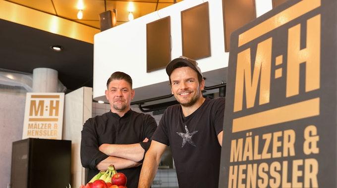"""Tim Mälzer und Steffen Henssler stehen im Studio der neuen Kochshow """"Mälzer und Henssler liefern ab!"""" bei Vox"""