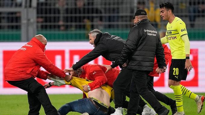 BVB-Trainer Marco Rose versucht zwischen den Ordnern und dem Flitzer zu schlichten.