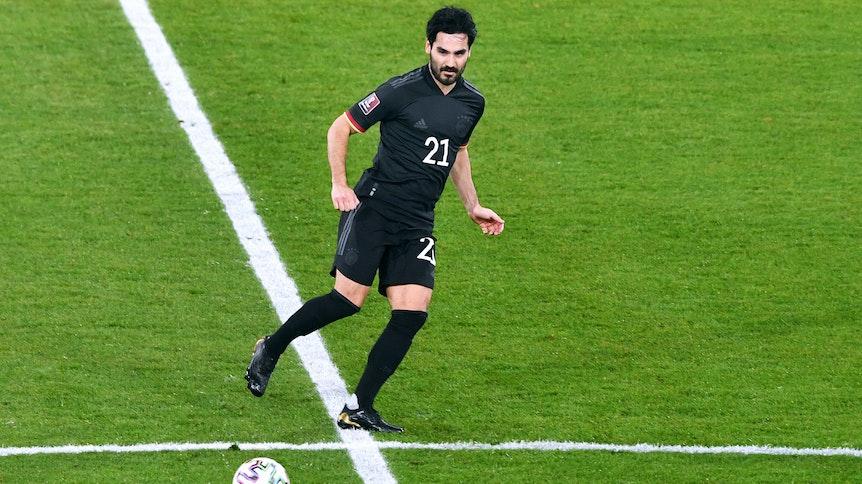 Mittelfeldspieler Ilkay Gündogan beim WM-Qualifikationsspiel der deutschen Nationalmannschaft gegen Island am 25. März 2021. In dieser Szene spielt er am Mittelkreis einen Pass zu einem Mitspieler.