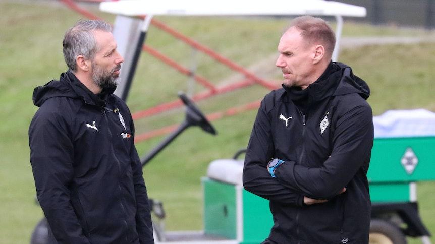 Gladbachs Trainer Marco Rose (l.) und Co-Trainer Alexander Zickler (r.), sich zugewandt im Gespräch, beim Training der Gladbacher am 23. Februar 2021 auf dem Trainingsgelände des Borussia-Parks.
