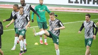 Gladbachs DFB-Nationalspieler Florian Neuhaus (l.), Matthias Ginter (M.) und Jonas Hofmann (r.) beim Aufwärmen vor Borussias Bundesliga-Duell am 15. Mai 2021 bei Werder Bremen.