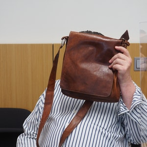Hinter einer braunen Herren-Schultertasche verbirgt der angeklagte Betrüger im Düsseldorfer Gerichtssaal sein Gesicht.