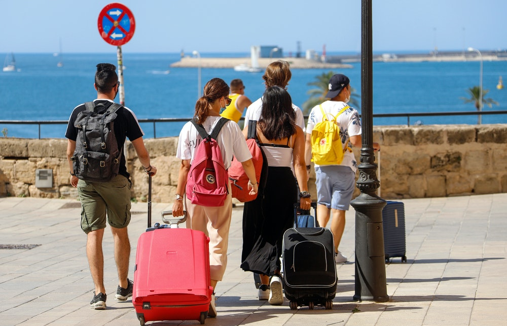 Touristen gehen im Juni 2021 mit ihren Rollkoffern durch die Urlaubsinsel Mallorca.