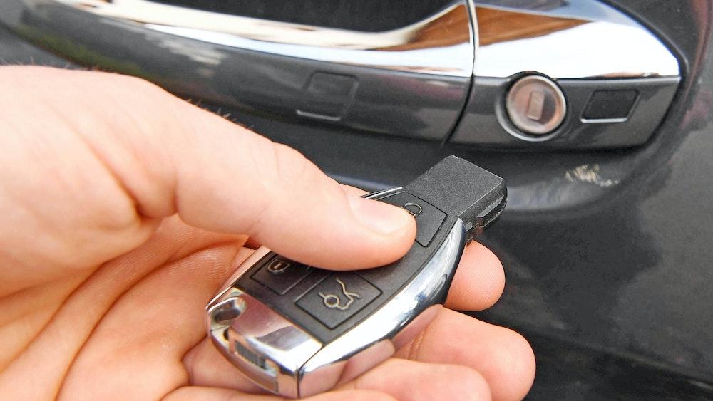 Eine junge Frau hält einen Autoschlüssel in der Hand. Durch einen Knopfdruck lassen sich alle Fenster gleichzeitig herunterfahren.