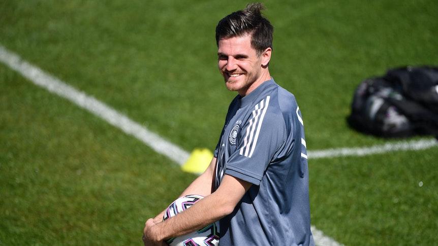 Nationalspieler Jonas Hofmann lächelt, derweil hält er einen Ball in seinen Händen.