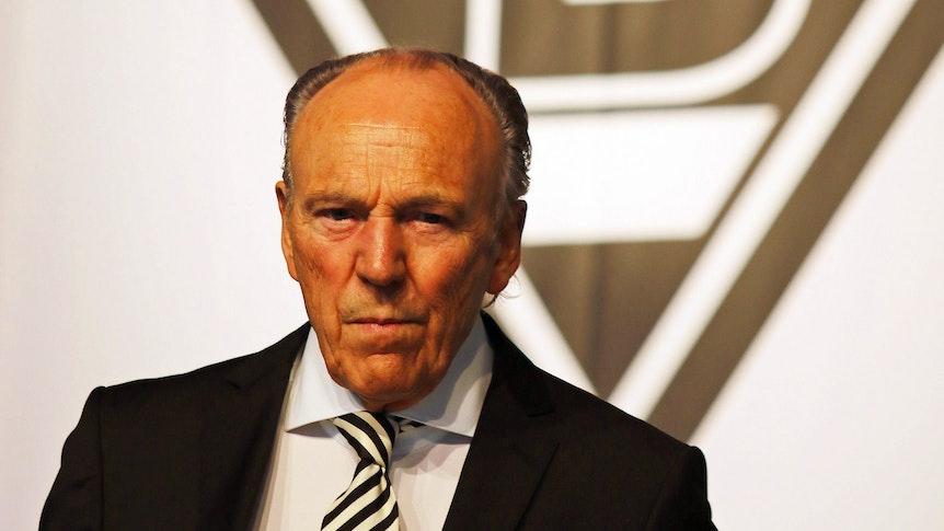 Gladbach-Präsident Rolf Königs steht vor einer Borussia-Fahne und blickt mit ernster Miene in die Kamera.
