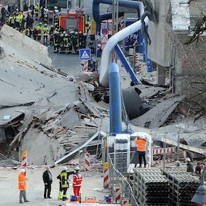 Zahlreiche Einsatzkräfte stehen vor den Trümmern des eingestürzten Stadtarchivs.