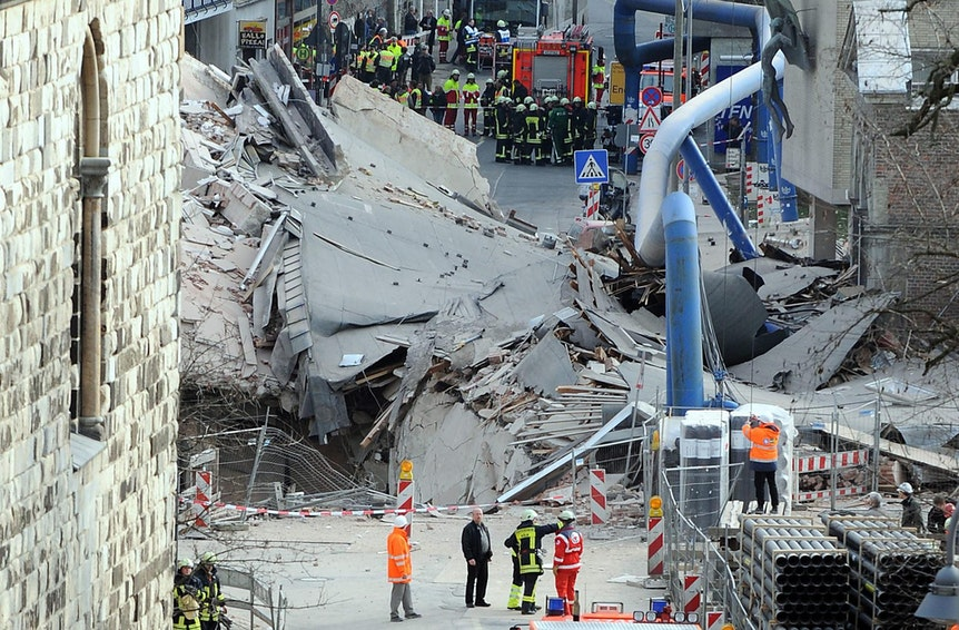 Das eingestürzte Stadtarchiv: Trümmer auf der Straße, Einsatzkräfte stehen daneben.