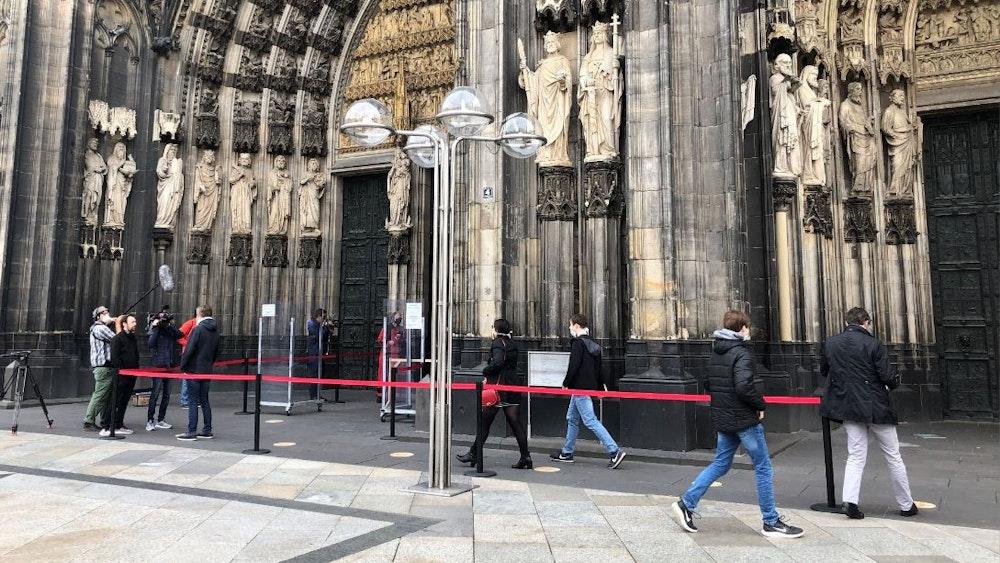 Besucher warten am Eingang des Kölner Doms.