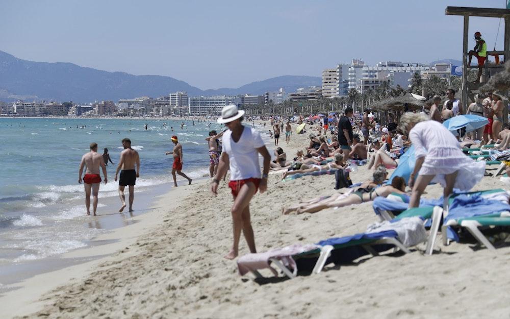 Touristen halten sich am Strand von Arenal in Palma auf Mallorca auf