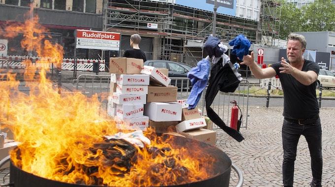 Jenke von Wilmsdorff wirft Klamotten in ein Feuer in Köln. Foto von der dpa, honorarfrei