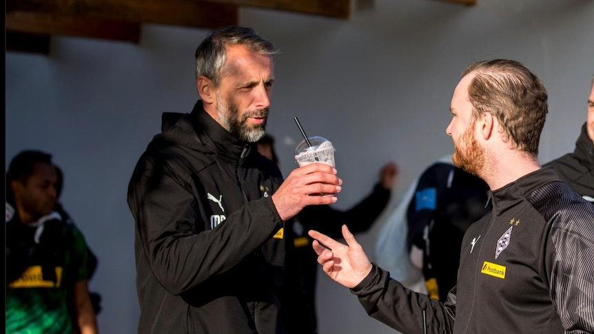 Trainer Marco Rose von Borussia Mönchengladbach bekommt nach dem Training von Melf Carstensen einen Shake gereicht.