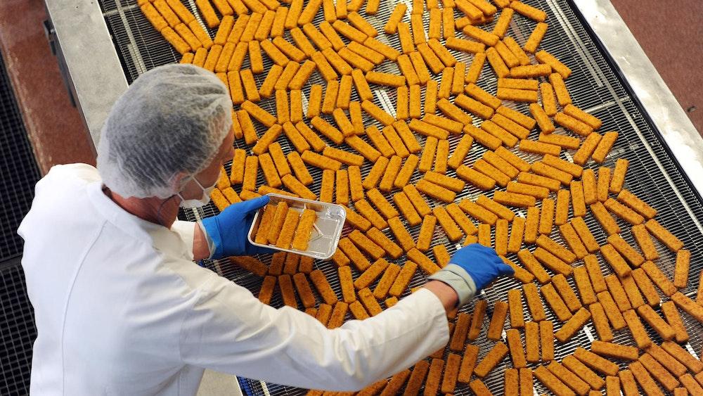Ein Mitarbeiter kontrolliert Fischstäbchen bei Frosta. Die Verbraucherzentrale hat Produkte untersucht, die auf Fisch verzichten.