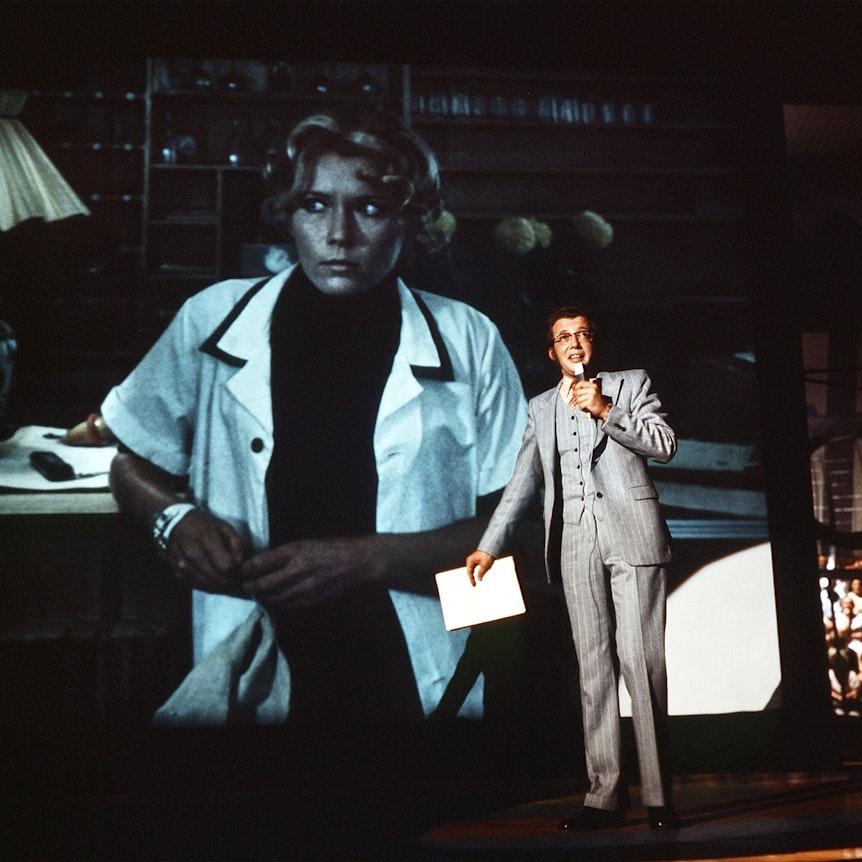 """TV-Film """"Das Millionenspiel"""" (1970): Dieter Thomas Heck als Moderator Tilo Uhlenhorst im Studio spricht mit einer Hotelangestellten (auf der Videowand im Hintergrund)"""