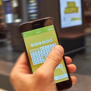Hand hält Smartphone, auf dem Zahlen für Eurojackpot getippt werden.