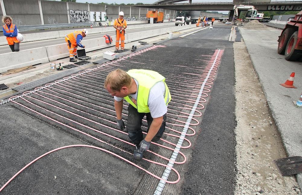 Ein Arbeiter bringt auf einem Testgelände neben der A3 Rohrleitungssysteme an.