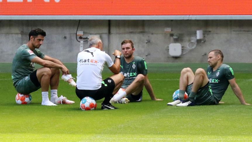 Gladbachs Christoph Kramer (Mitte) nach der Trainingseinheit am 4. Juli 2021 im Gespräch mit seinen Teamkollegen Lars Stindl (links) und Tony Jantschke (rechts) sowie Trainer Adi Hütter (vorne) im Borussia-Park.