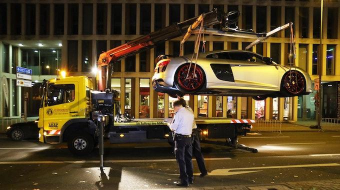 Unter den Augen der Kölner Polizei wird ein Sportwagen auf den Abschlepper geladen.