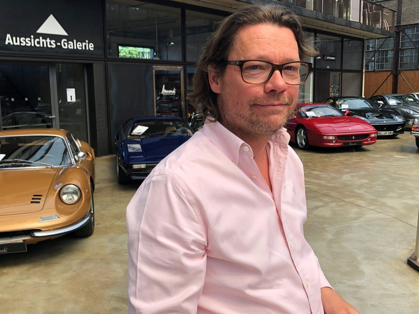 Bernhard Kerkloh, Inhaber und Geschäftsführer von Movendi in seinem Verkaufsraum, in dem zahlreiche Oldtimer stehen.