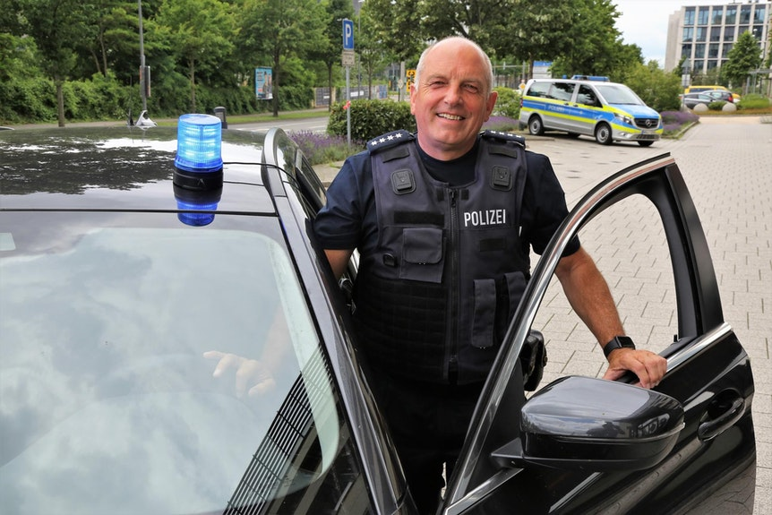 Jürgen Berg (59), Leiter der Einsatzgruppe Verkehr der Kölner Polizei, steht an seinem Einsatzwagen.