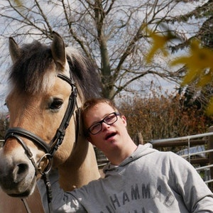 Ein junger Klient des Zentrums für therapeutisches Reiten in Köln Porz steht neben einem Therapiepferd.
