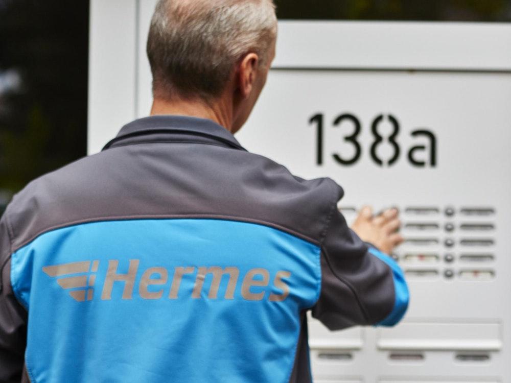 Ein Hermes Paketbote klingelt an der Tür eines Wohnhauses.