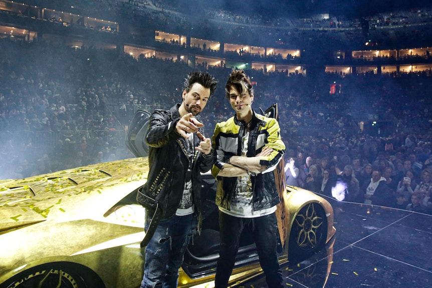 Andreas und Christian Ehrlich posieren in der Show-Pause vor ihrem goldenen Super-Flitzer in der Lanxess-Arena.