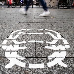 Corona-Piktogramme wurden als Hinweis auf die Maskenpflicht auf einem Bürgersteig in Düsseldorf gesprüht.