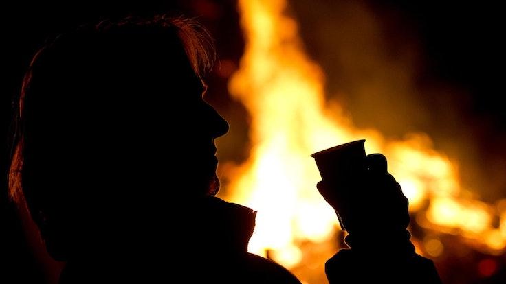 Die Silhouette eines Menschen setzt sich auf diesem undatierten Foto vor einem Feuer ab.