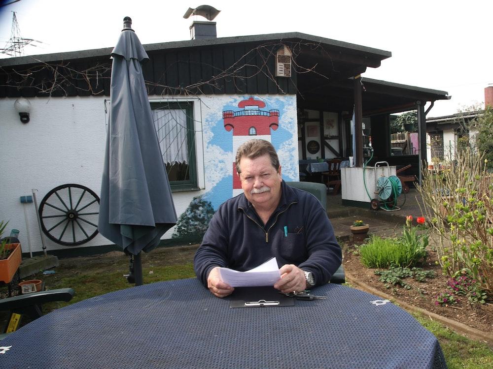 Hans Gilson sitzt an einem Tisch in einem Kleingarten.