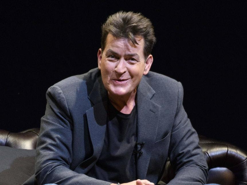 Charlie Sheen sitzt während einer Pressekonferenz gelassen auf einem Ledersofa.