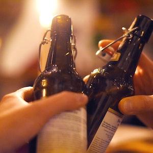 Auch alkoholfreies Bier kann Alkohol enthalten. Ein Experte erklärt die Details. Unser Foto zeigt zwei Personen beim Anstoßen – in diesem Fall mit alkoholhaltigem Bier.