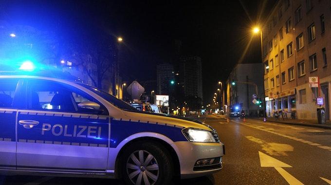 Ein Polizeiauto steht mit Blaulicht in Köln-Höhenhaus auf der Straße.
