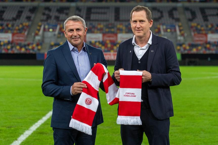 Uwe Klein (r.) und Klaus Allofs posieren mit dem Schal von Fortuna Düsseldorf.