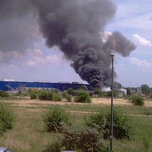 Dichter Rauch steigt aus dem brennenden Gebäude auf.