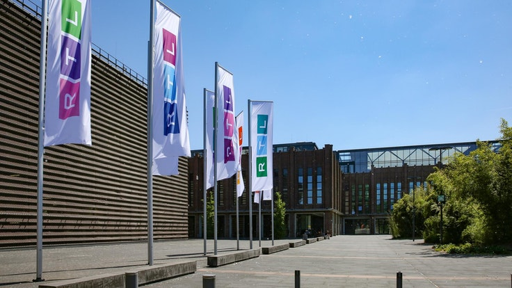 Die Fahnen am RTL-Sitz in Köln-Deutz sind bereits ausgetauscht. Auf jeder Fahne sind andere Farben angeordnet. Das Foto wurde am Sonntag (13. Juni) aufgenommen.