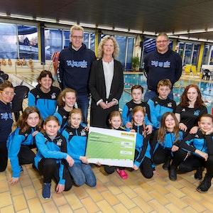 Christiane Jansen, Geschäftsführerin von WestLotto, überreicht den Spendenscheck an den Schwimmverein Olympia Borghorst.