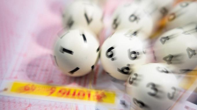Lottokugeln liegen auf Tippschein
