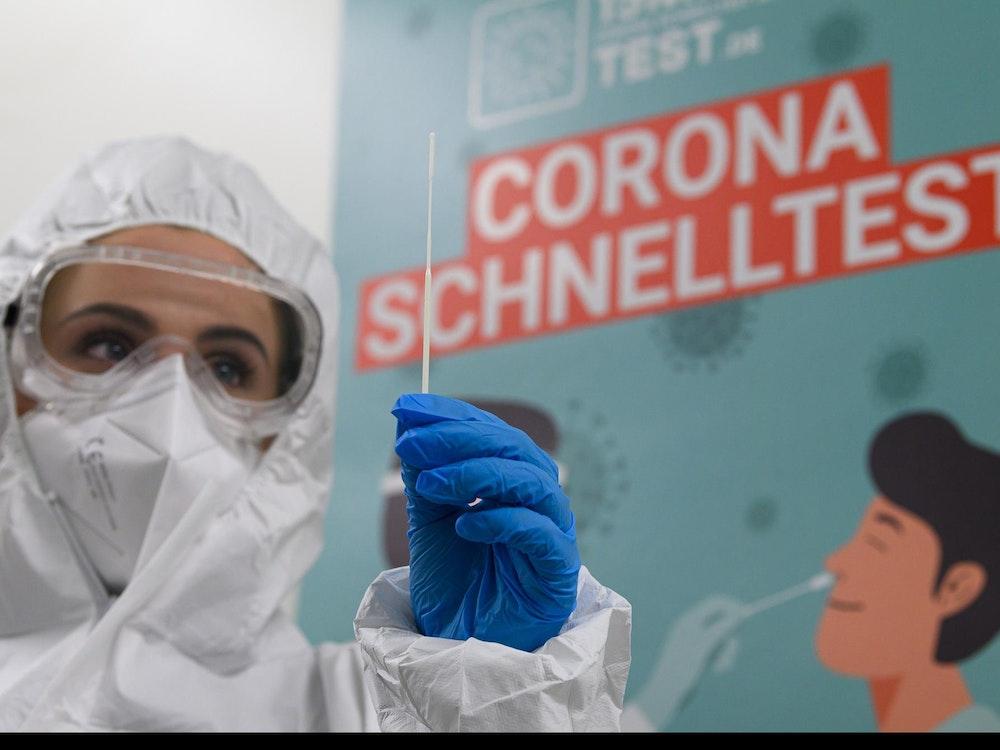 Mitarbeiterin in Schutzanzug bereitet Corona-Test vor