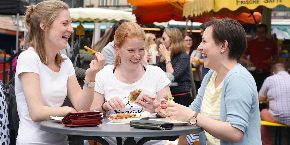 """Die Studentinnen (v.l.) Franziska Pleis (23), Charlotte Kalenberg (22) und Lisa Neumann (22) testen zum ersten Mal den veganen Bi-Bu-Stand. Alle haben einen Falafel-Burger bestellt, eine Portion Fritten wird geteilt. """"Super lecker!"""", sagt Franziska. Lisa: """"Das ist einfach mal eine gelungene Abwechslung zur Mensa."""""""