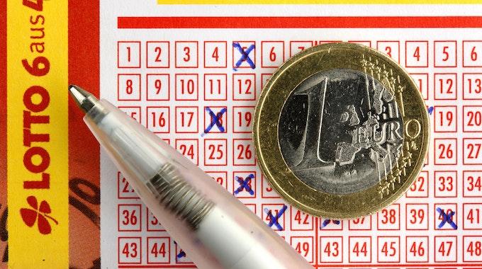 Euro-Münze liegt auf ausgefülltem Lottoschein