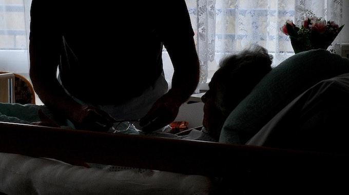 Ein Pfleger hilft einer im Bett liegenden Frau.