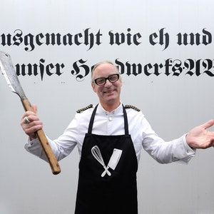 Peter Inhoven vor dem alten Wahlspruch seiner Metzgerei in Wersten.